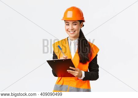 Smiling Satisfied Asian Female Construction Engineer Leading Inspection At Enterprise, Wearing Safet