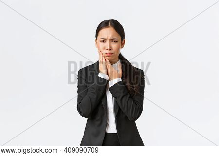 Female Asian Office Manager In Black Suit Having Toothache At Work. Troubled Businesswoman Holding H