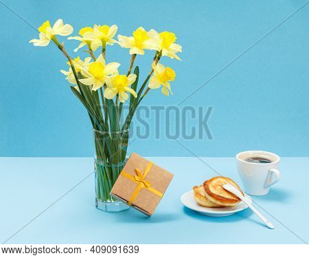 Bouquet Of Yellow Daffodils In Glass Vase, A Gift Box, A Cup Of Coffee And Plate With Pancakes On Bl