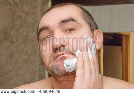 Man Smears His Face With White Shaving Foam. Preparing To Shave Your Beard Home. Close-up. Male Faci