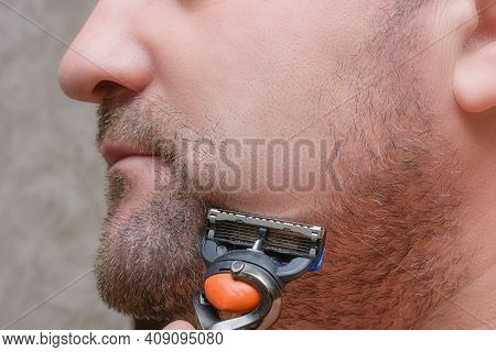 Man With Stubble On Cheek. Shaves Beard With Razor. Male Facial Care Concept.