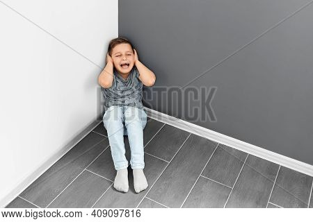 A Boy Of 7-10 Years Old Sits In A Corner On The Floor And Cries. Punishing Children. Bad Learning.