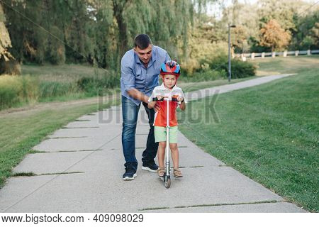 Caucasian Father Dad Training Teaching Boy Son To Ride Scooter. Preschooler Child Kid In Helmet With