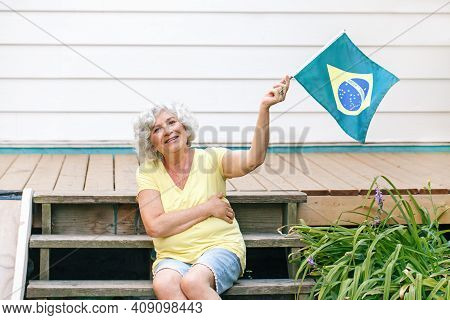 Proud Citizen Celebrating Independence Day Of Brazil. Happy Old Woman Holding Brazilian Flag Outdoor