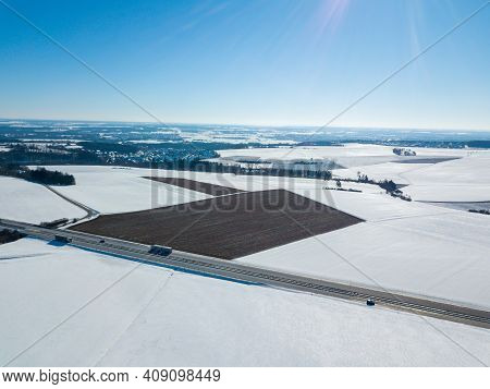 Aerial Drone Shot Of A German Autobahn With Cars Driving Next To Snow Covered Fields On A Sunny Wint