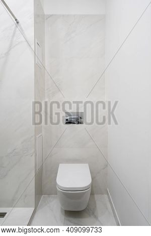 Vertical View Of Bright Modern Restroom With New Ceramic Toilet Bowl Against White Tiled Copy Space