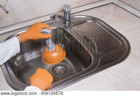 Woman's Hands With Orange Gloves Cleaning Sewer At Kitchen Faucet Over Metal Sink. Close Up Of Hand
