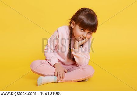 Lovely Little Girl Sitting On Floor With Crossed Legs, Keeping Palm On Chin, Looking Bored At Camera