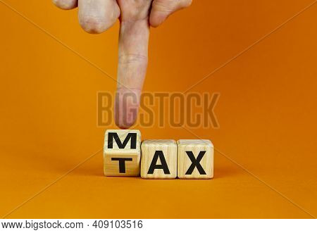 Max Tax Symbol. Businessman Turns The Wooden Cubes With Words 'max Tax'. Beautiful Orange Table, Ora