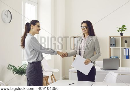 Happy Business Woman And Client Smiling And Shaking Hands Confirming Business Deal