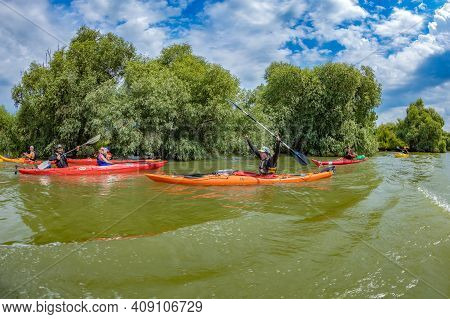 Murighiol, Romania - July 20, 2020: Friendly Young Sportsmen Practicing Kayak-canoeing On An Arm Of