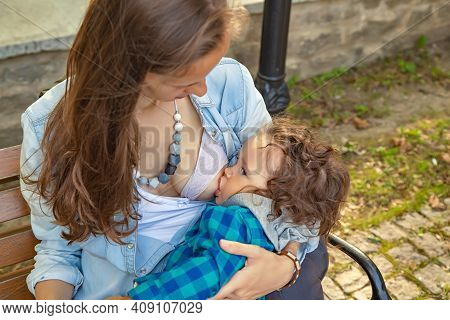 Portrait Of Modern Long-haired Mother Breastfeeding Her Little Baby Outdoors In A Secluded Place On