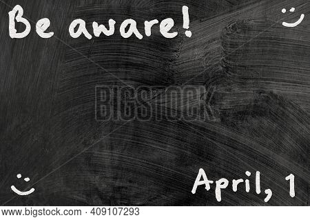 Be Aware On Blackboard Note Over A Dark Background. April Fools Day
