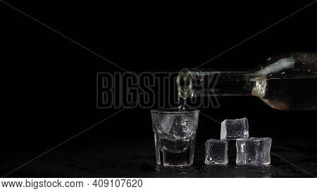 Shot Glass On Black Table. Barman Hand Pours Vodka, Tequila Or Sake From Bottle Into Empty Shot Glas