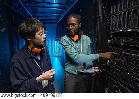 Waist Up Portrait Of Two Young Technicians Setting Up Server Network While Working In Data Center
