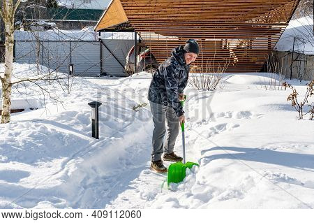 A Worker Cleans Snow From The Garden Paths With A Shovel On A Sunny Day. Garden Maintenance In Winte
