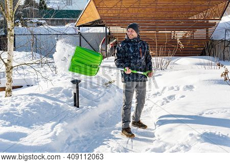 An Adult Man Cleans The Paths In The Garden From Snow In A Good Mood. Shoveling Snow From Paths With