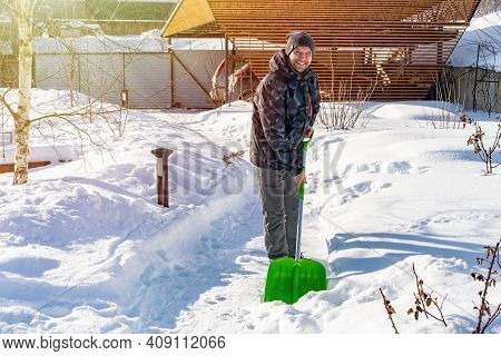 An Adult Smiling Man Cleans Snow From The Tracks With A Shovel After Heavy Snowfall On A Sunny Day.