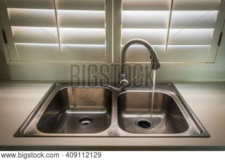 Sink In A Kitchen With Running Tap Water