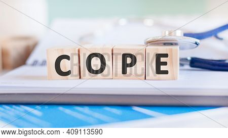 Wooden Block Form The Word Cope With Stethoscope On The Doctor's Desktop. Medical Concept.