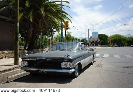 Mendoza, Argentina - January, 2020: Old Vintage Low Rider Car On The Street Under Palm Trees. Classi