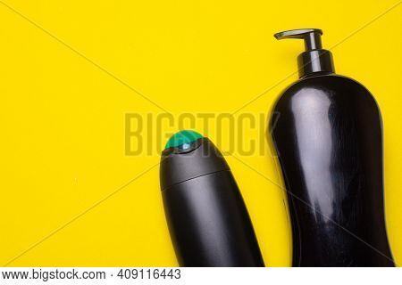 Black Shampoo On The Background Of Copyspace. A Bottle Of Shampoo. Yellow Background. Article About