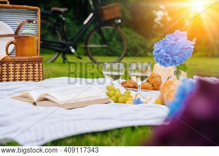 Summer Picnic On Sunny Day With Bread, Fruit, Bouquet Hydrangea Flowers, Glasses Wine, Straw Hat, Bo