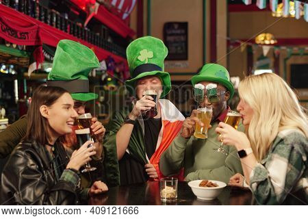 Group of friends in green hats sitting at the table drinking beer and celebrating Patricks Day in the bar