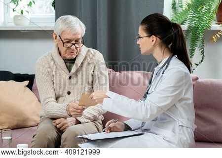 Young brunette general practitioner showing paper with her medical recommendations to sick senior man while consulting him in living-room