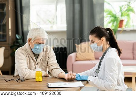 Young female general practitioner in whitecoat and protective mask touching pulse of sick senior male patient during medical check-up