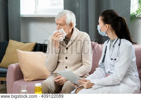Young female general practitioner with digital tablet looking at sick senior man with handkerchief by his face sitting on couch in front of her