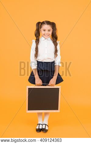Preparing Small Child For School. Small Girl Holding Black-board On Yellow Background. Small Kid Wit