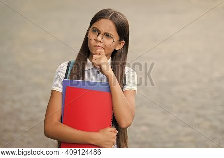 Serious Little Kid In Glasses Hold School Books With Thoughtful Look Outdoors, Imagination.