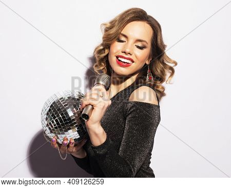 Young blond woman dressed in evening dress holding a microphone and disco ball, singing and smiling over white background