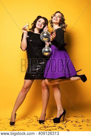 Two beautiful elegant women celebrate party and drinking champagne. Best friends wearing dress and holding disco balls. Bright make up, red lips. over yellow background.