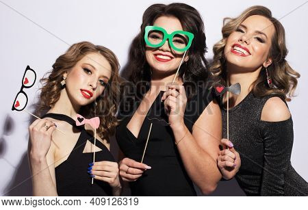 Beautiful women friends in black cocktail dresses with party props, fake glasses and mustache, all for fun and joy.
