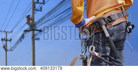 Rear View Of Electrician With Safety Belt And Work Tools Is Preparing To Work On High Altitude With