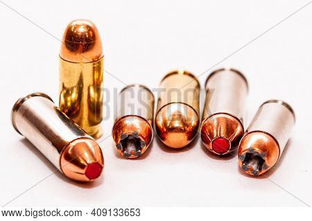 Six Bullets, Hollow Point And Full Metal Jackets, 45 Caliber, 9mm And 44 Special Lined Up On A White