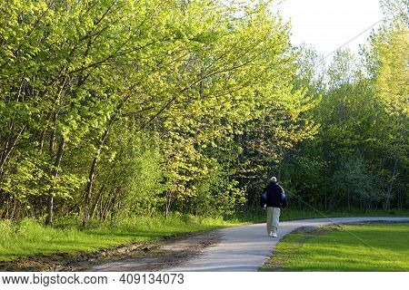 Man Walking In The Public Park In Springtime.