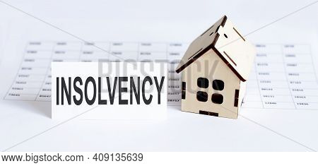 Closeup Of House Wooden Model With Blank And Text Insolvency On Chart Background.