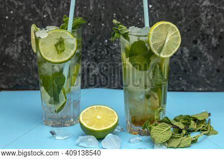 Glass Of Mojito Cocktail With Mint And Lime Ice Cubes  With Fresh Limes. Sparkling Refreshing Water.