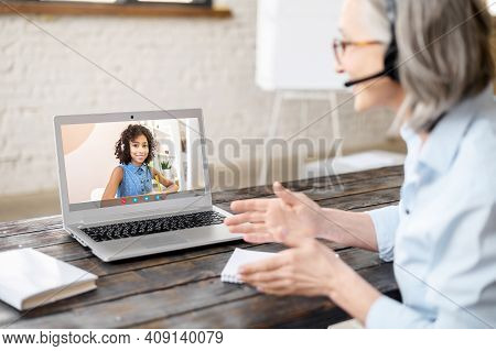 Mature Gray-haired Female Teacher In Headset Looking At Screen, Teaching Young Lady, Having Virtual