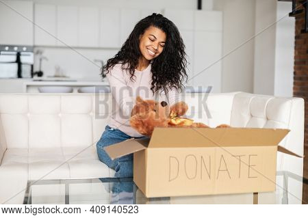 Kind Smiling African American Female Volunteer With Curly Hair Sitting On A Sofa, Packing Toys In A