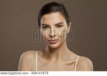 Beautiful Face With Cosmetics Cream. Spa Woman On Clear Skin On Brown Background