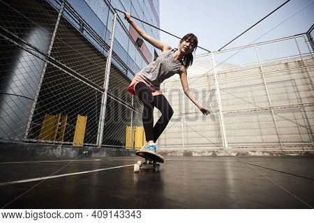 Beautiful Young Asian Female Skateboarder Practicing Skateboarding Outdoors