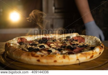 Fresh Hot Italian Pizza With Cheese And Steam On The Table In A Pizzeria. Food Delivery.
