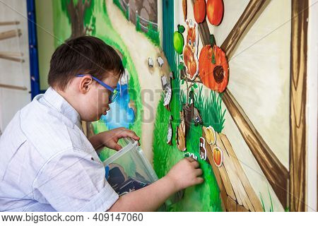Editorial. A Teenage Boy With Disabilities Plays With Pictures On A Magnetic Board. Down Syndrome, A