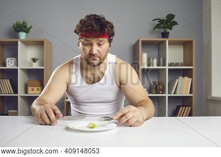 Sad Man On Strict Diet Sitting At Table And Looking At Tiny Piece Of Apple On Plate