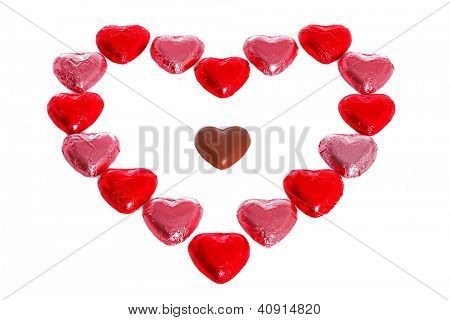 Chocolate hearts in red and pink foil wrappers on a white background, with one unwrapped heart in amongst the group.