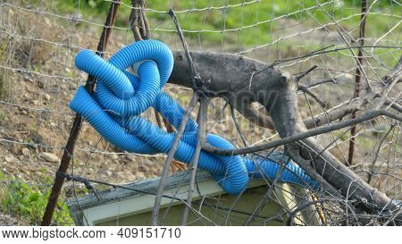 Blue Plastic Conduit Tubing Tied In Knots Around Fence Post